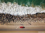 Drone view of waves hitting the rocks next to the highway with a vászonkép, poszter vagy falikép