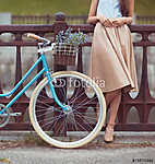 Young beautiful, elegantly dressed woman with bicycle vászonkép, poszter vagy falikép