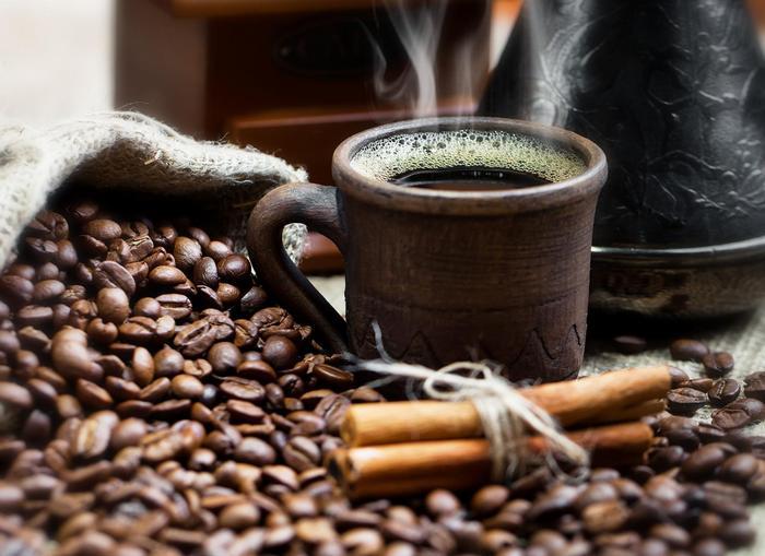 Egy csésze gőzölgő kávé, barna csészében,
